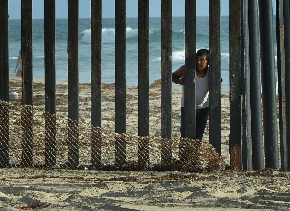 A man looks out toward the U.S. from the Mexican side of the border fence that divides the two countries in San Diego on August 20, 2014. Photo source: Getty Images.