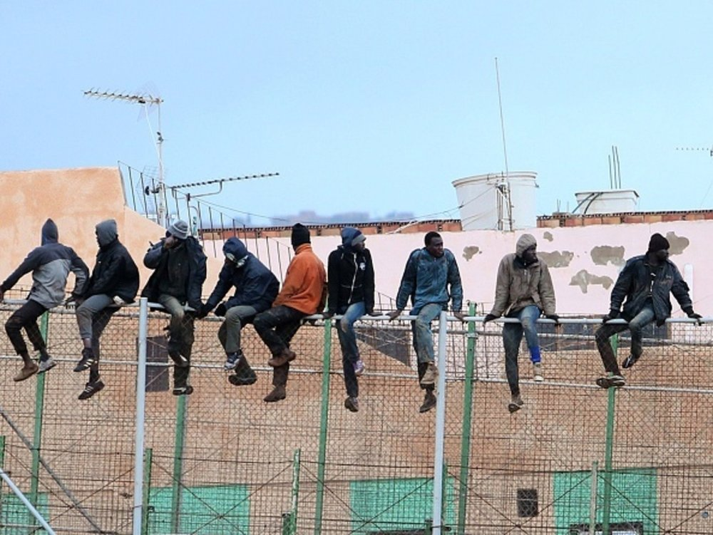 Migrants climbing over the border fence between Morocco and Melilla. Photo source: AFP.