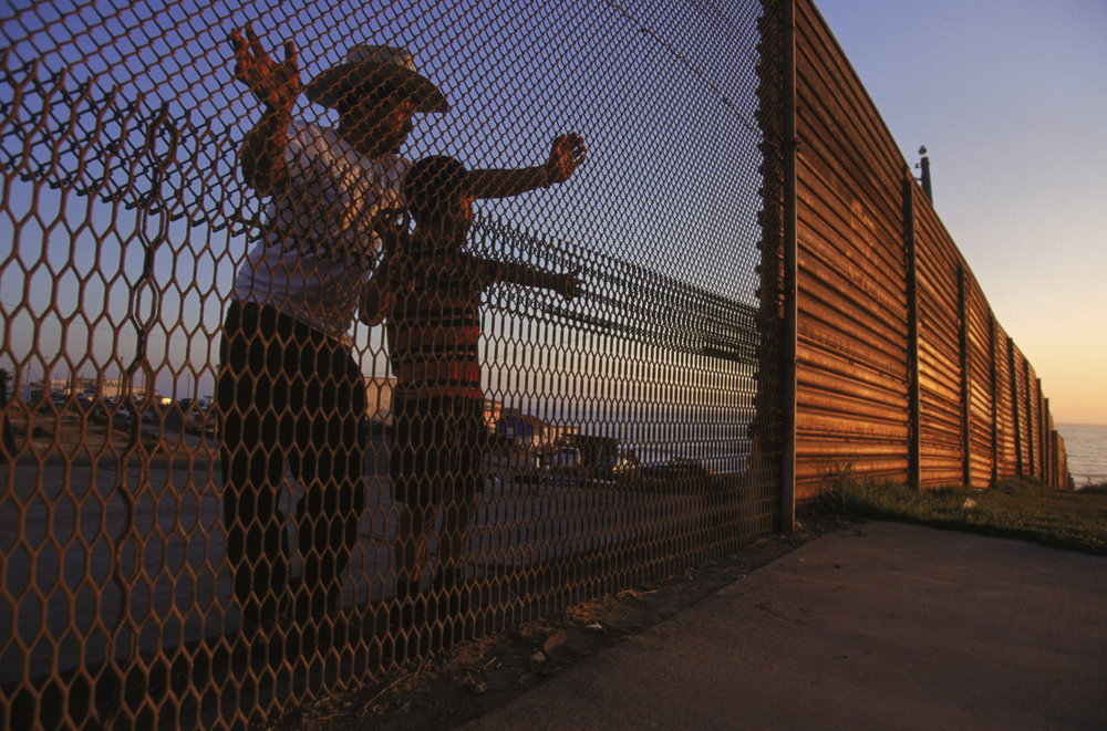 A father and son peer through the international boundary into the United States from Tijuana, Mexico. Photo by Todd Bigelow.