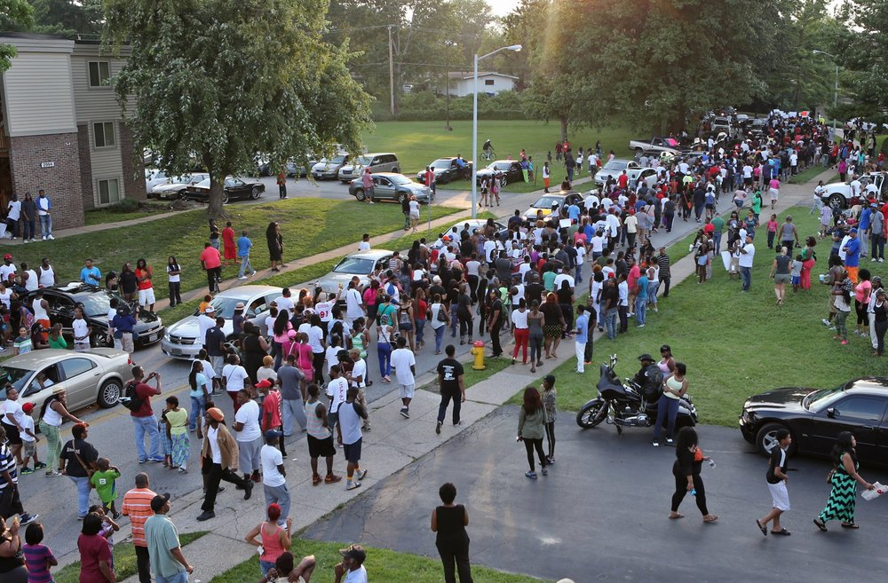 A large crowd of protesters marches out of the apartment complex on Sunday evening, Aug. 10, 2014, in Ferguson, towards W. Florissant, as they protest the shooting of Michael Brown. Photo by J.B. Forbes.
