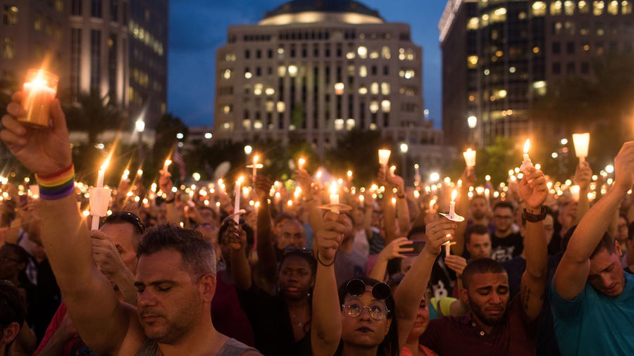 People hold candles during an evening memorial service for the victims of the Pulse Nightclub shooting at the Dr. Phillips Center for the Performing Arts, June 13, 2016 in Orlando, Florida. Photo by Drew Angerer / Getty Images