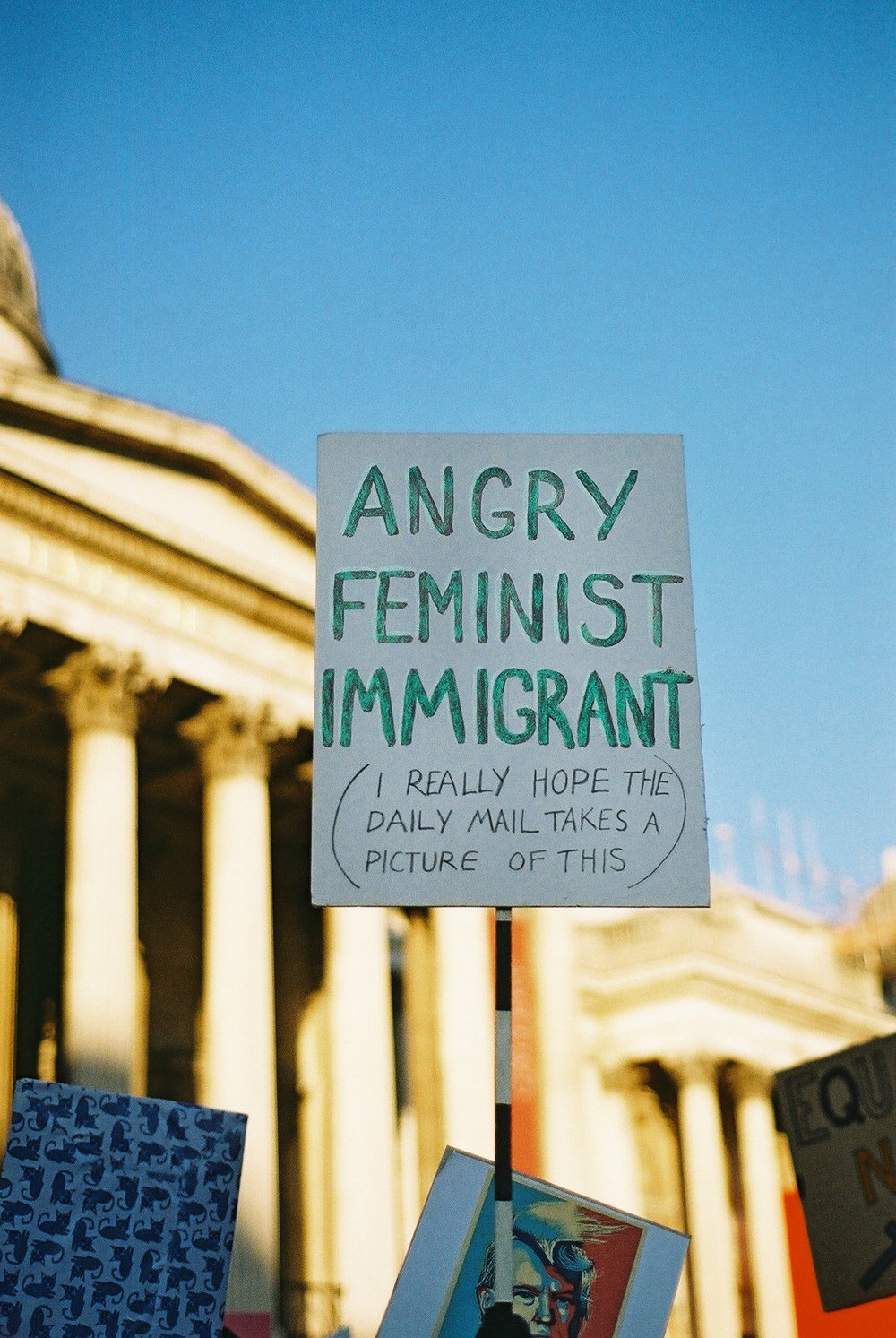 "A protestor holds a poster with the words ""Angry Feminist Immigrant"" at the Women's March day in London, 2017. Photo by Camilla Glorioso."