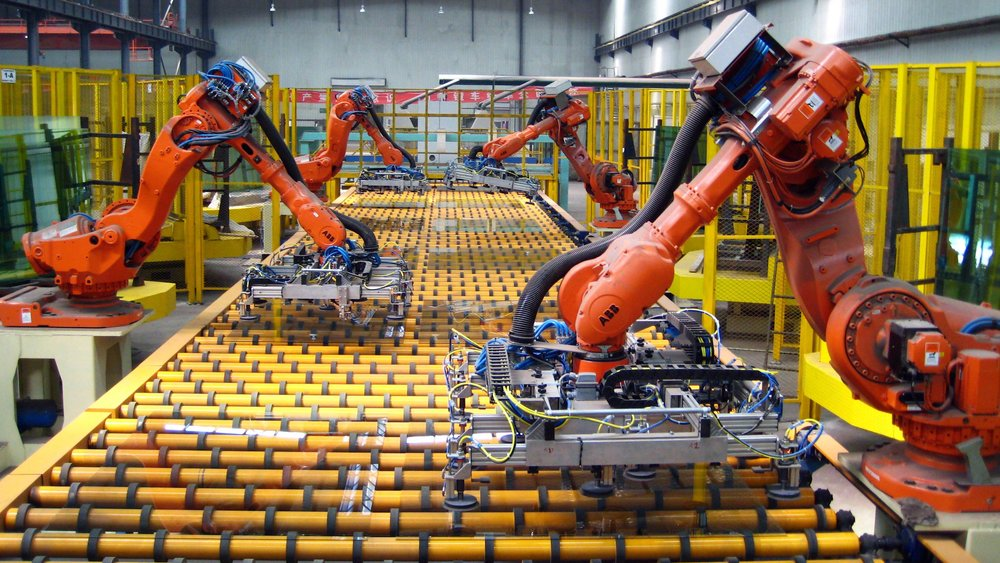 Large pieces of plate glass are unloaded by robotic arms in a factory in UK. Photo source: Getty Images.