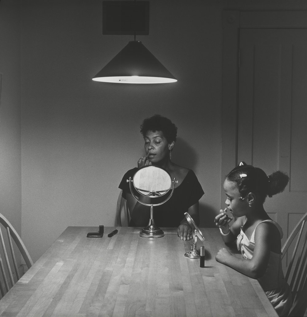 Woman and daughter with makeup from  Kitchen Table  series, 1990 by Carrie Mae Weems.