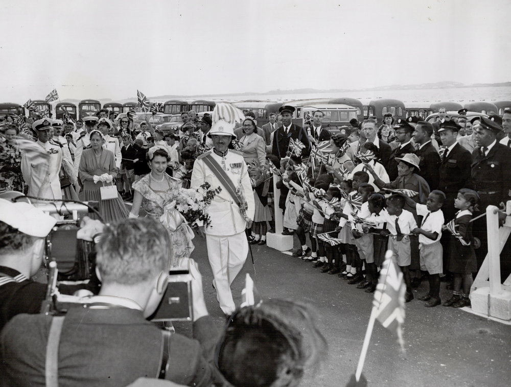 The Queen accompanied by Sir Alexander Hood, Governor of Bermuda is greeted by flag-waving children, 1953. Photo source: Virtual Reference Library.