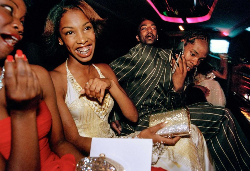 "Crenshaw High School girls selected by a magazine to receive ""Oscar treatment"" for a prom photo shoot take a limo to the event with their dates, Culver City, California, 2001 by Lauren Greenfield."