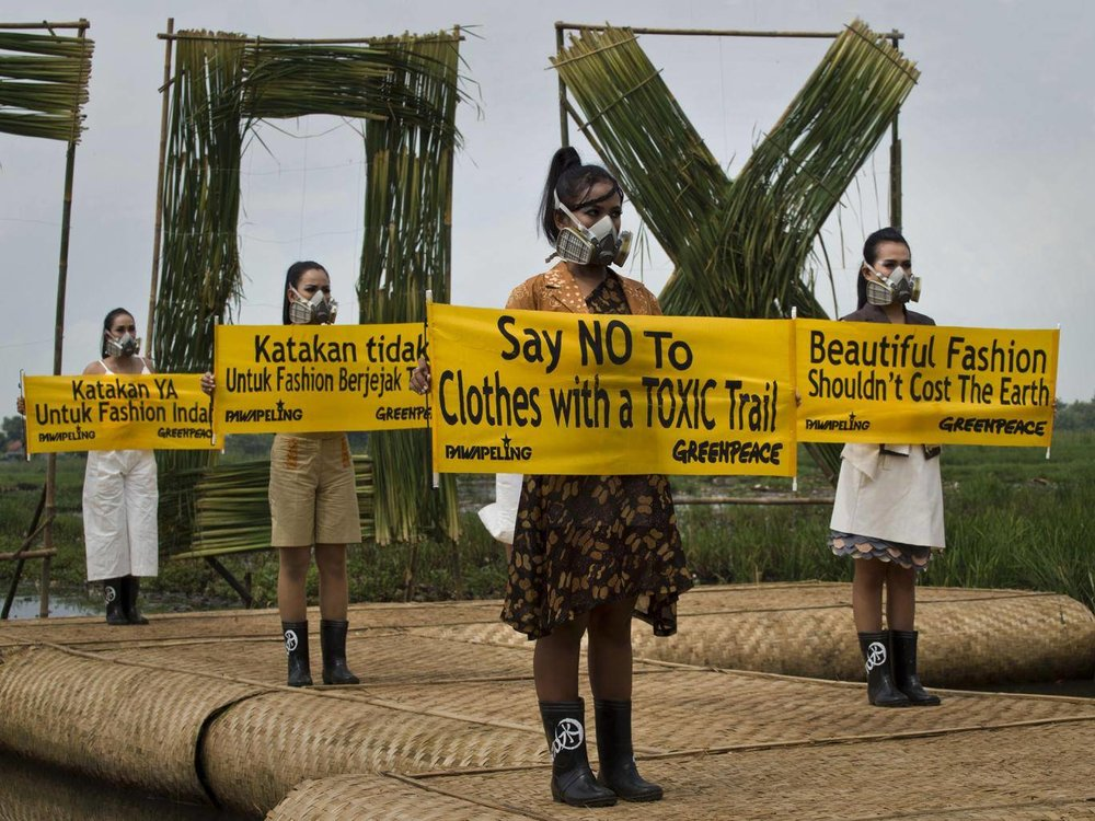 Models with gas masks – part of a Greenpeace campaign for top fashion brands to remove toxic chemicals from their supply chains in Indonesia. Photo source: AFP/Getty Images.