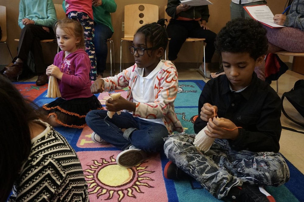 Photo by Eilif Ronning, Media Intern Kids get to work tying the first part of their corn husk dolls.