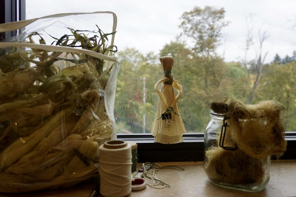 Photo by Elif Ronning, Media Intern A finished corn husk doll sits on the window sill surrounded by harvested husks, corn silk and string.