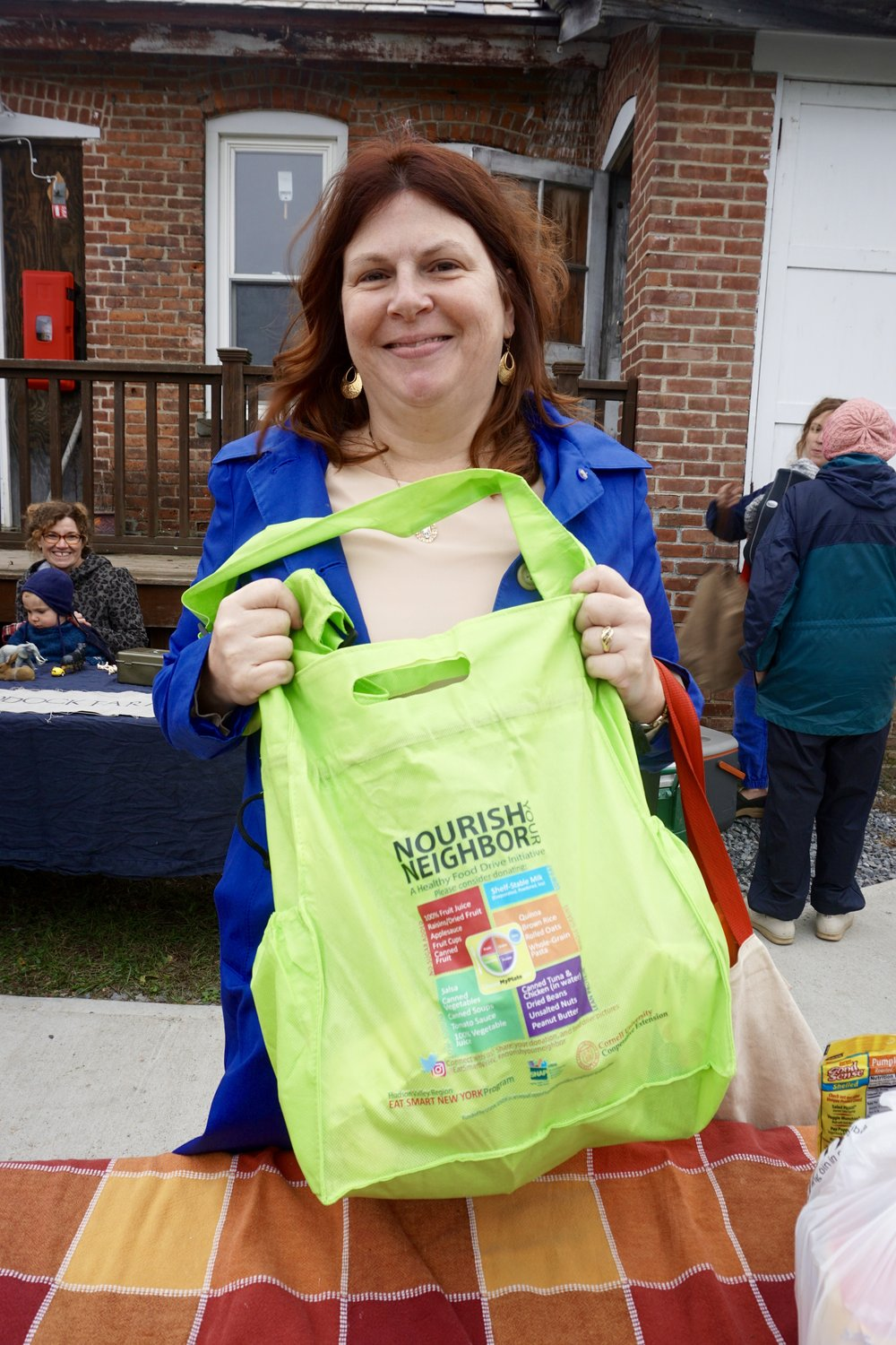 Mary Ficht, Teacher at Warring School, drops off a bag of healthy shelf-stable items for the Nourish Your Neighbor Food Drive