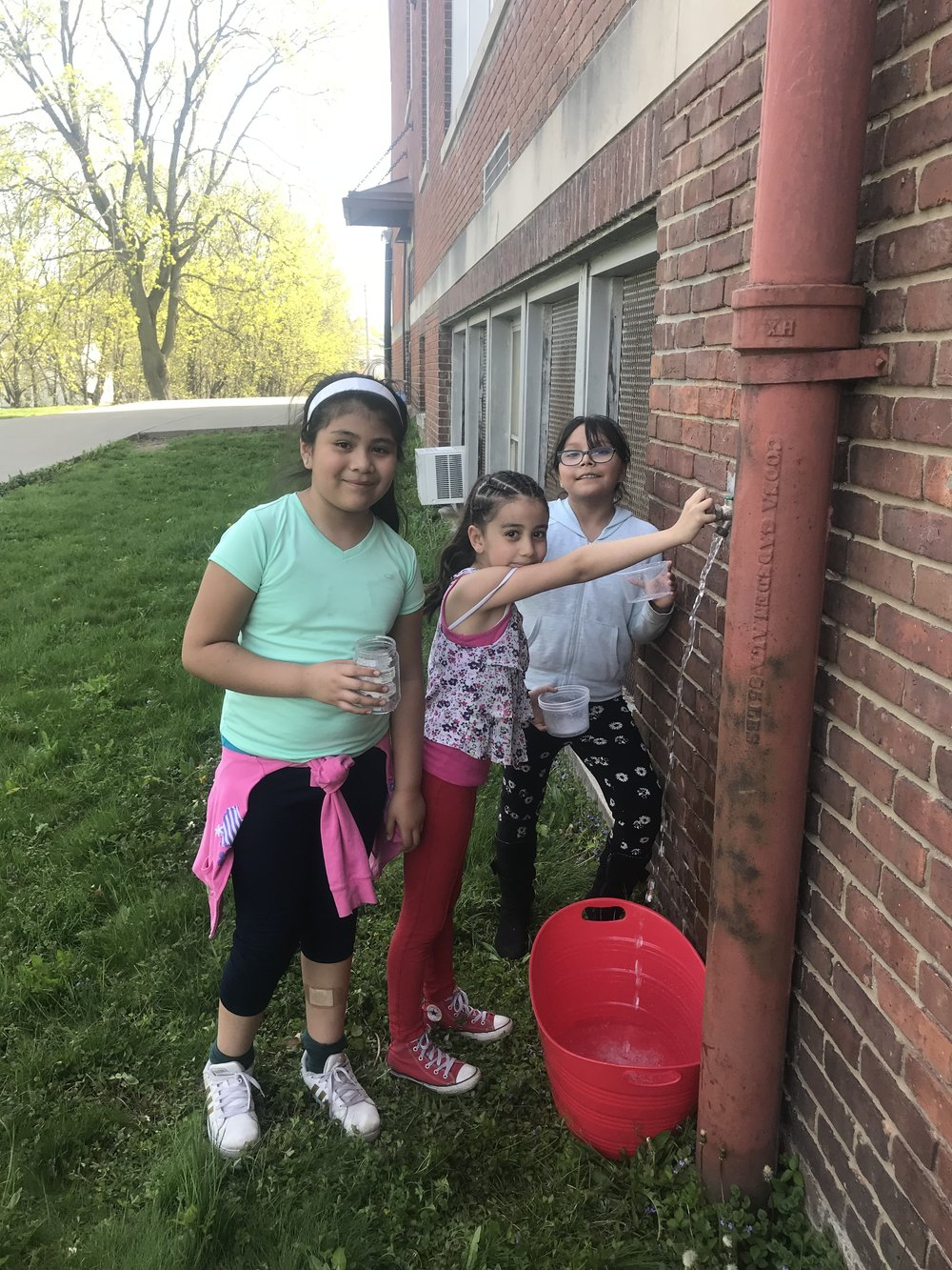 Morse students fill a bucket of water for the garden.