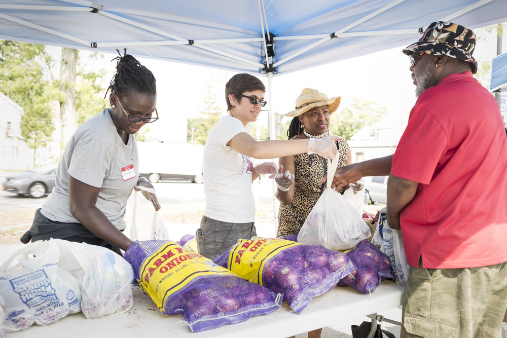 Bintou Hinds, Jamie Levato, and Ozie Williams distribute produce at Dutchess Outreach's Free Farm Stand. Photo credit: Sean Hemmerle