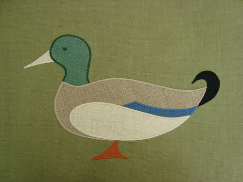 "A dignified mallard duck, shown above in natural, jade, tangerine, blue & ecru on sage - a festival of colors! Mallard applique is 11"" wide. $50.00 per motif."