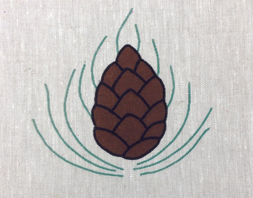 """Pine Cone: A medallion that can be turned at at45 degree angle to become a corner motif,shown here in brown, black and sage, 6 1/2"""" from bottom to highest needle, $36.00"""