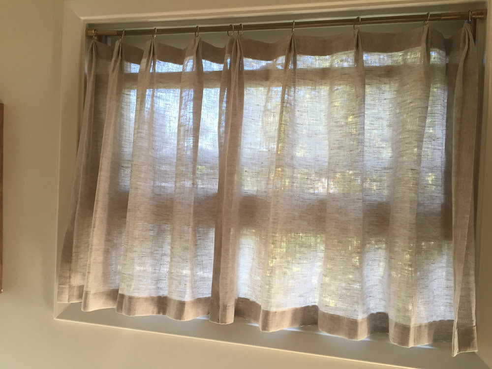 Cafe style curtains in the kitchen are 1 1/2 fullness with pleated top and rings. Fabric: Handkerchief Linen - Natural