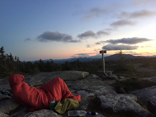 Hulk bundled up in the Kelty bag watch the sunset from East Baldpate