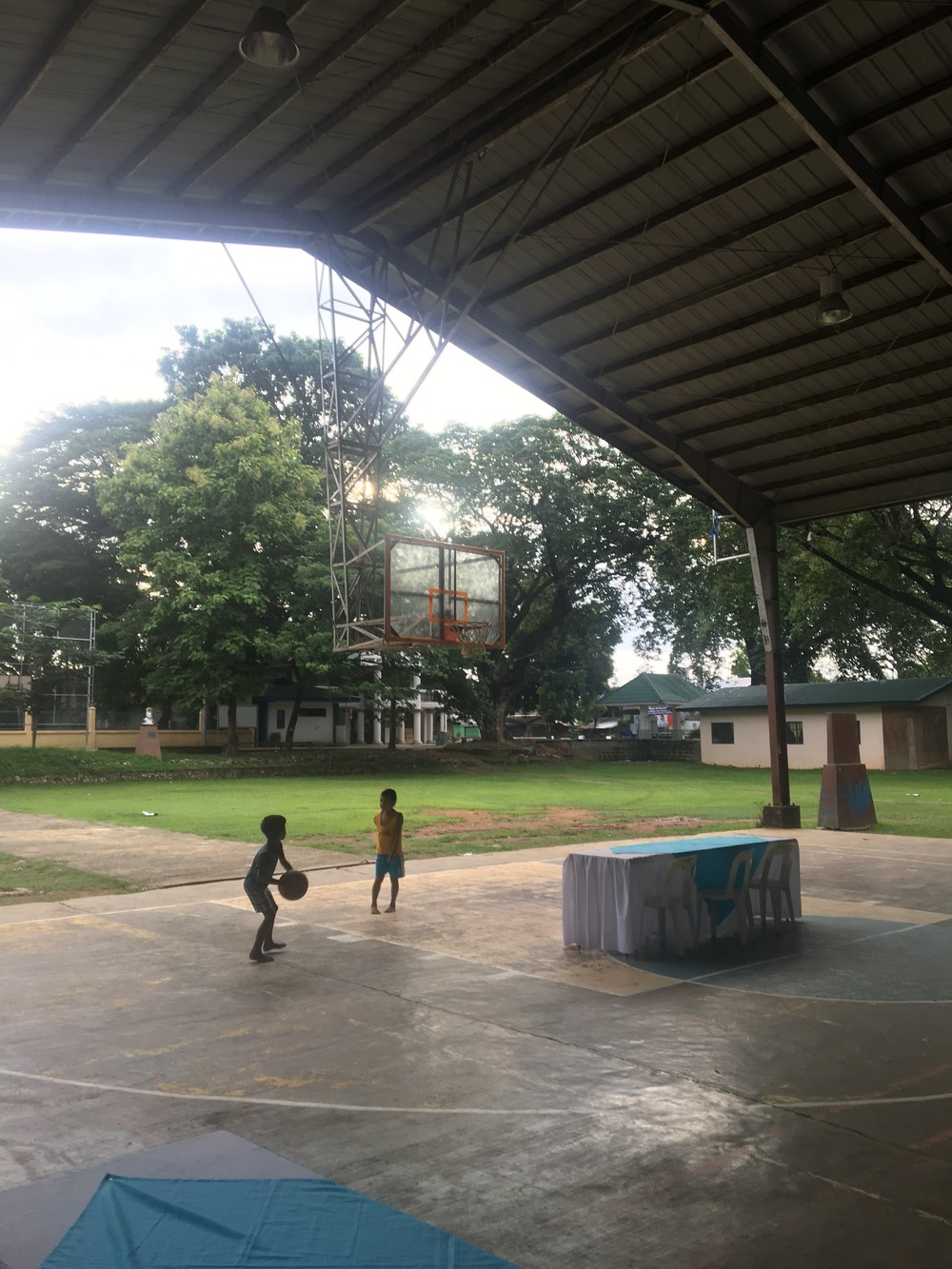 Kids playing basketball at the pavilion.