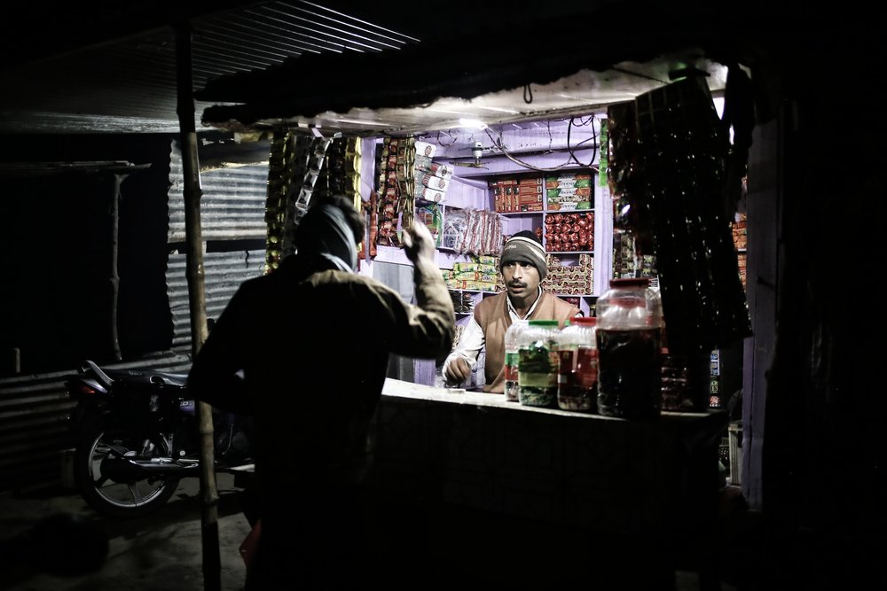 Small kiosk lit up by microgrid solar. Photo via SunFunder