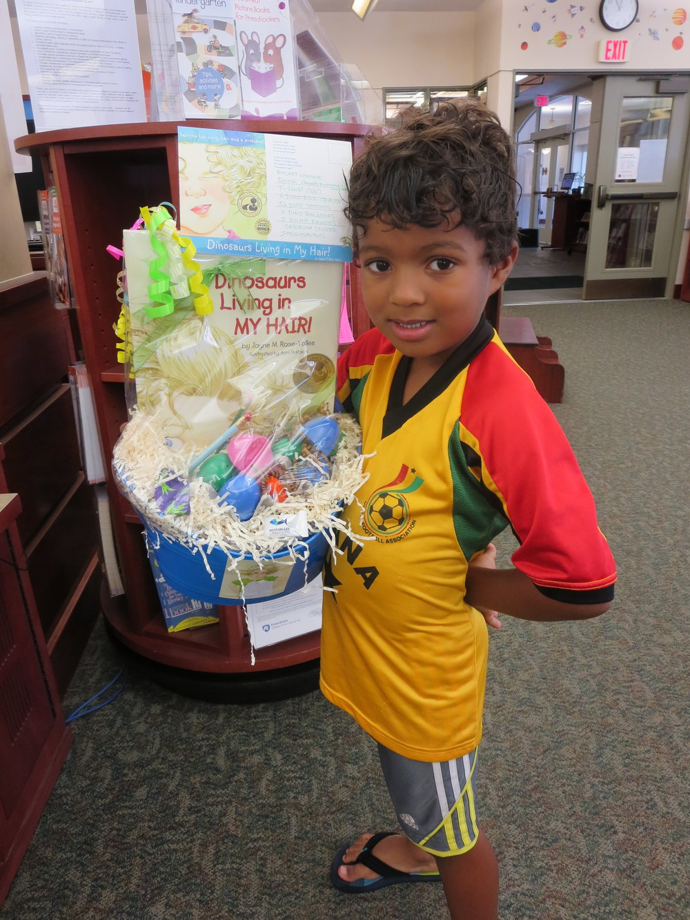 """Hello DLIMH followers!  Meet Julian, happy winner of our fun-loaded """"dinobasket"""" offered to participants in Schlow Centre Region Library Children's Summer Reading Program in State College, Pennsylvania. Kids earn tickets for prizes by reading books and dropping the tickets into boxes set out next to each prize, displayed on the book cases all summer as incentives. Our young winner's curly hair appears to have serious dino potential which might be what led him to our box (aside from all the cool dino stuff)!  DLIMH illustrator Anni Matsick is guesting today, here to tell everyone about our fun-filled prize awarded recently at her community library and how you can make a """"dinobasket"""" of your own!"""