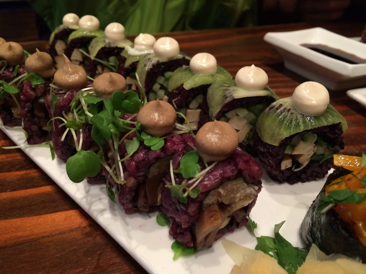 Crunch N' Munch Roll (right)- Black rice, Alfafa sprouts, English cucumber, Tofu, Kiwi Sauce: White Miso  Mighty Mushroom Roll (left)- Six-grain rice, Enoki, Tofu, Shiitake, Micro arugula Sauce: Shiitake Teriyaki