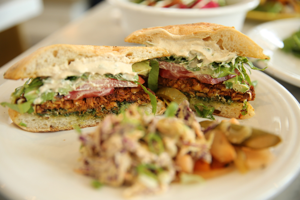 Sandwich |  YO SOY FUERTE mexican torta : housemade tempeh chorizo, cilantro pumpkin seed pesto, tomato, shredded romaine, avocado, chipotle cashew, crema, salsa verde, roated tomatillo sauce, slow fermented ciabatta, side of mexican coleslaw and spicy pickled vegetables  (pictured above and below)