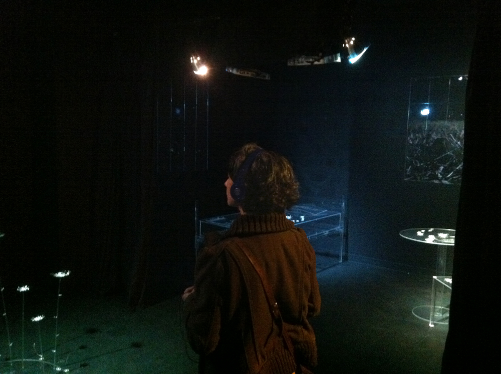 A viewer listens to sound on headphones as she walks through the installation.