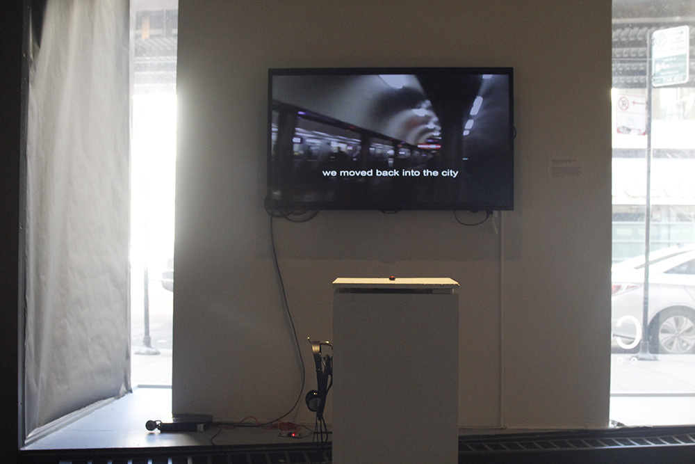 The viewer presses a button to advance the text while video footage plays short clips of both nature and city scenes. Headphones play a continuous soundtrack of a young girl speaking.
