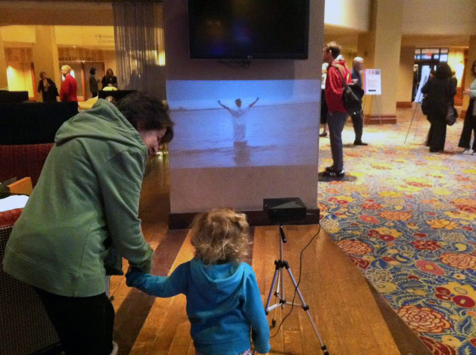 Passers-by watch the festival videos in the lobby of the Sheraton Hotel in Washington, D.C.