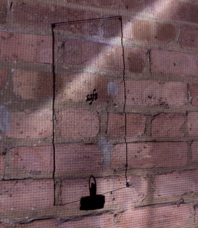 A shadow of the window as the projection passes through it onto a brick wall.