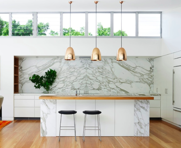Kitchen featuring marble and gold pendants.