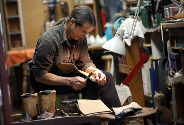 Michael Anthony Carnacchi trimming uppers to Lincoln boots