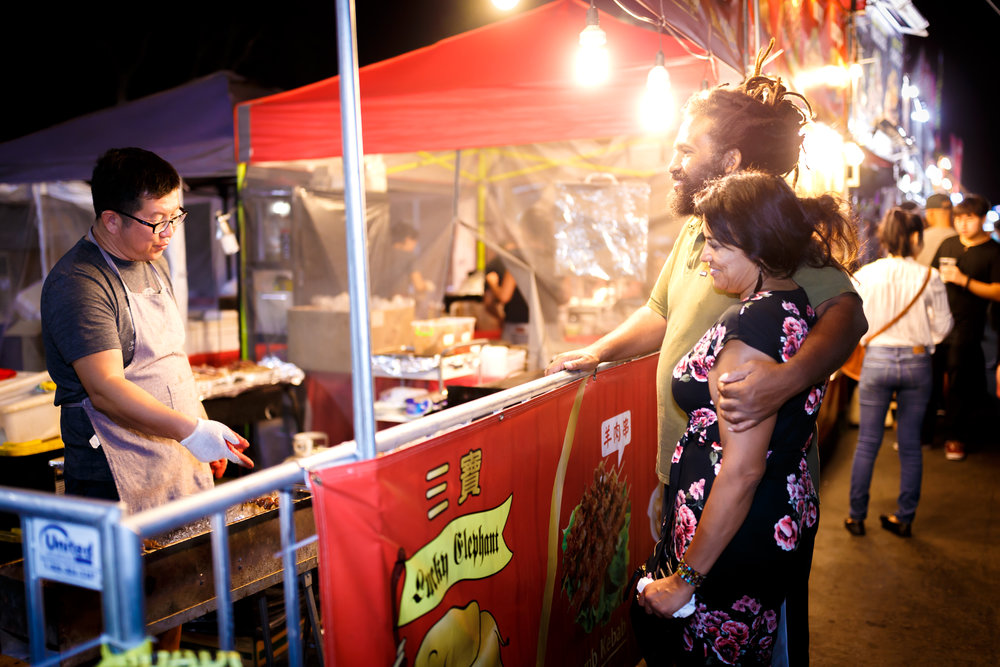 A cute couple watches vendor Lucky Elephant grill some tasty street snacks. Photo by John Truong.