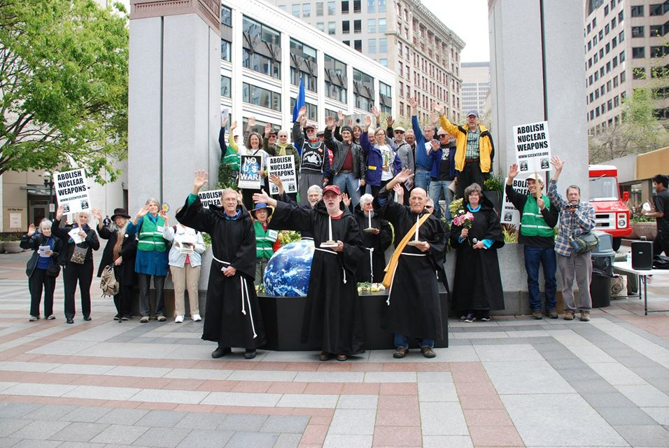 "Ground Zero Center for Nonviolent Action, in cooperation with other organisations, held the funeral for Mother Earth at Seattle's Westlake Center Plaza at noon today. Afterwards about 50 people waved goodbye to nuclear weapons. ""It was a truly energized wave."" (Leonard Eiger)"