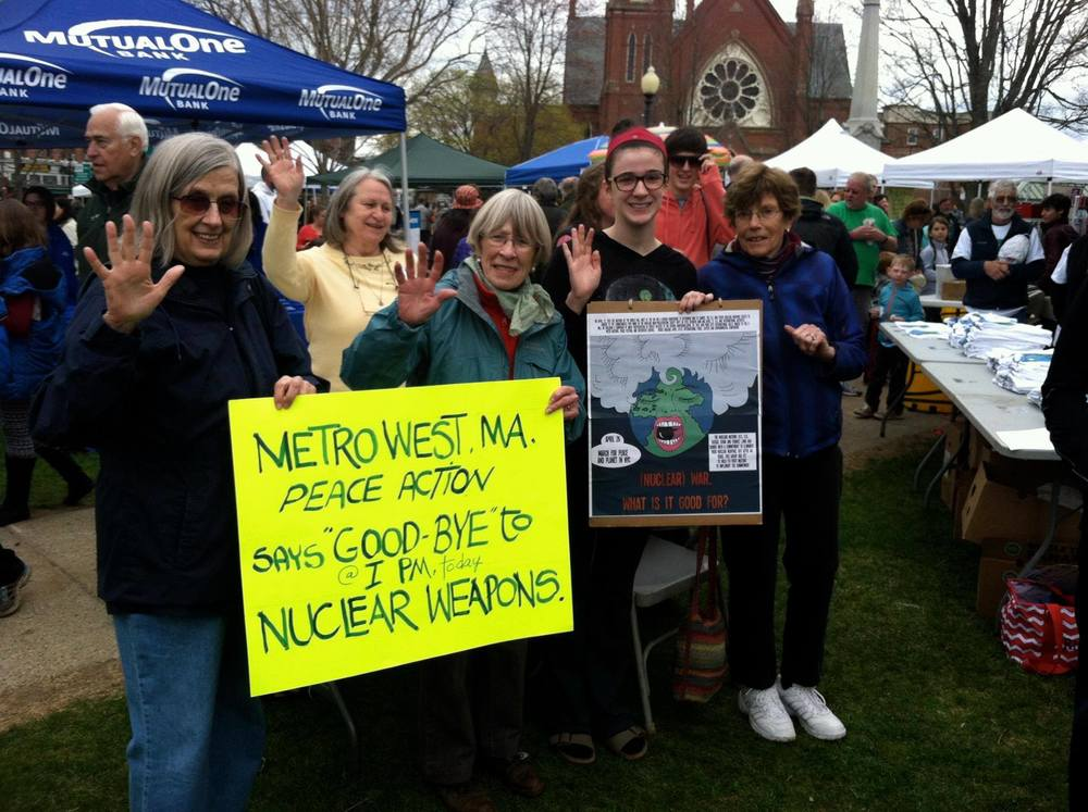 Metrowest Peace Action waved goodbye to nuclear weapons from Natick, Massachusetts' Earth Day celebration. 2nd from right is Natick high school student Isabella DeMarco, 2nd prize winner of Mass. Peace Action's student art contest, with her poster of Mother Earth screaming as she tries to rid herself of the Bomb