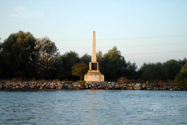 """Obeliscul din Crisan ridicat cu ocazia inaugurării lucrărilor de la marele M  """"Cette colonne a ete elevee en l'honneur de Sa Majeste Charles I-er, roi de la Roumanie, qui le 5/17 mai 1894 a daigne inaugurer la coupure du 8e au 18 miliaire""""  (Acest monument a fost ridicat în onoarea Majestății Sale Carol I, Regele Romaniei, care la 5/17 mai 1894 a binevoit să inaugureze a opta tăietură la mila 18). © info-delta.ro"""