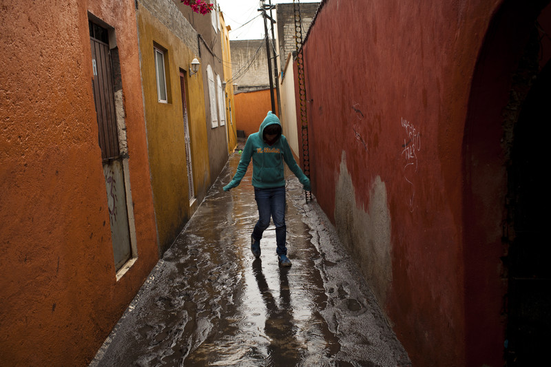 A resident in the south of Mexico City walks through the entrance to her home after heavy rainfalls produced a flash flood that has overspilled the city's sewage systen The city of Mexico produces an average of 40,000 liters (10,570 U.S. gallons) of sewage every second.