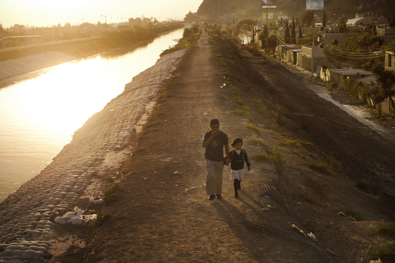 Father and child walk along the open sewage Canal de la Compañia in the municipality of Valle de Chalco on the periphery border of Mexico City and the state of Mexico. The Canal de la Compañia drains the Mexican capital of its waste. The canal lies several feet above thousands of homes and is a major source o pollution and fears of flooding which have occured in the past, destroying hundreds of homes.