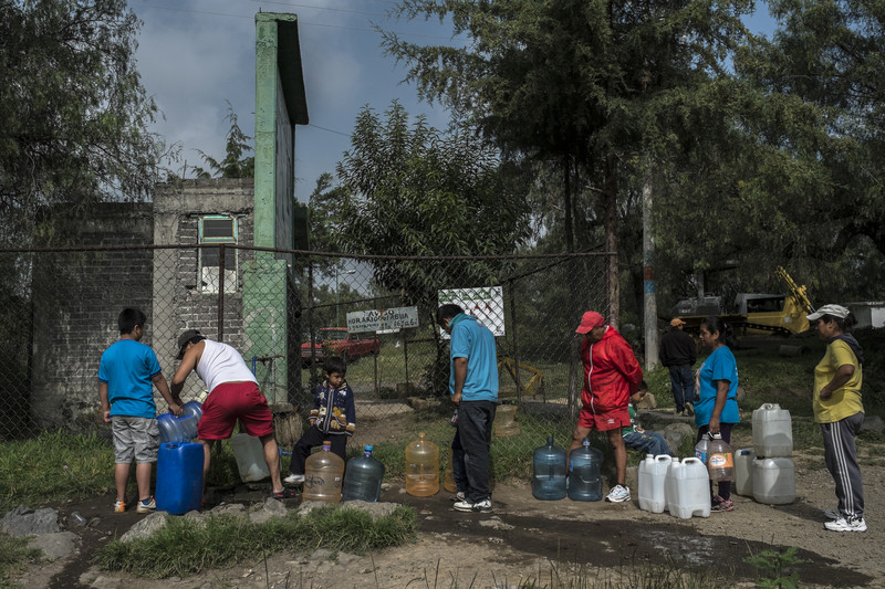 Residents of the southern district of Xochimilco in Mexico City line up to fenced well to collect drinking water. In theory only residents of the area are permitted to do so and in regulated hours. The residents once used to simply take water from the canals or from the springs but they have now been tapped and must feed the entire water system for the Mexican capital which suffers from water shortages.