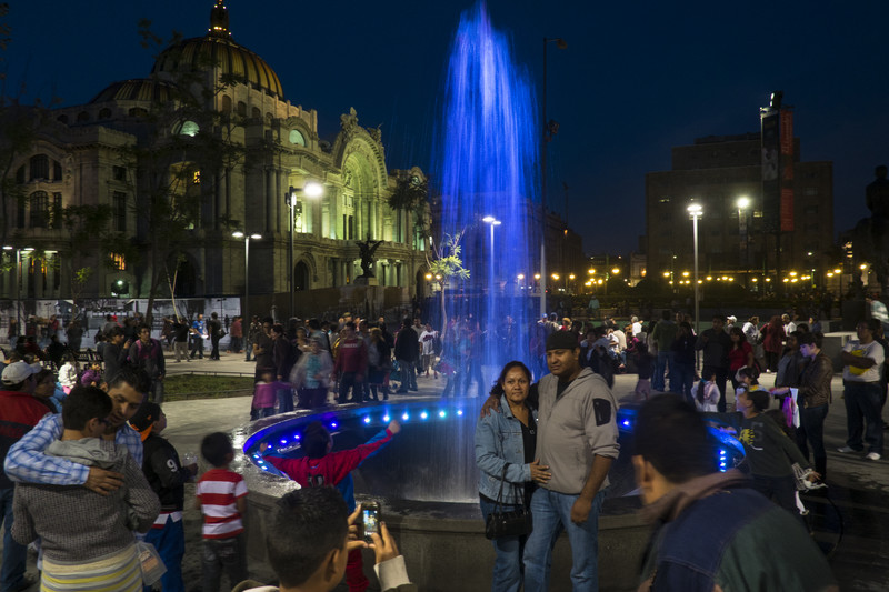 Mexicans enjoy a sunday night around a sewage suction pit with a water fountain at it's surface in downtown Mexico City.