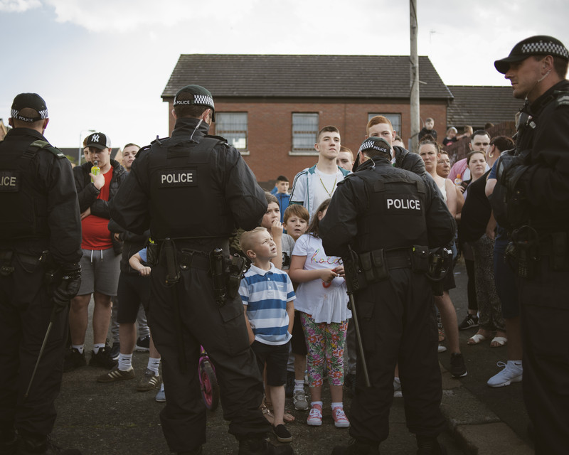 Police blocking passage for Catholic youth as Protestant Loyalist marching bands pass through the area on 12 July, flashpoint Clifton Street Service Sation, Catholic Irish Republican Carrick Hill area, Belfast