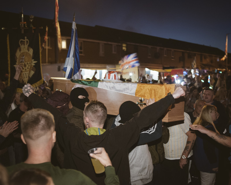 A coffin with the Irish flag is transferred by Loyalist paramilitary youth to be burned at a huge bonfire next to the so-called peace wall interfacing with Catholic Irish Republican neighbourhood of Falls.  As a yearly Protestant ritual, 11th Night bonfires are preceding Orange Order marches on Twelfth of July. The event is discussed highly controversial between the opposing communities in Northern Ireland, Protestant Loyalist Upper Shankill area, Belfast