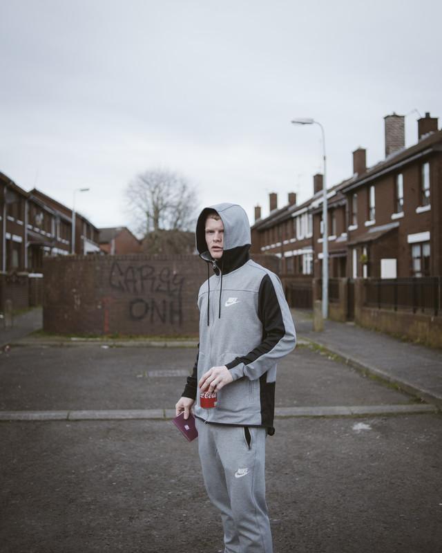 Jarlath holding an Irish passport he found on the street, Gibson St, Catholic Irish Republican Divis area, Belfast
