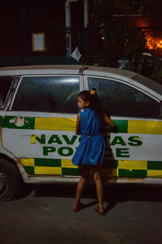 A girl writes on the window of a parked police car as a fire burns in the background.   NAVOTAS, MANILA. 2018.
