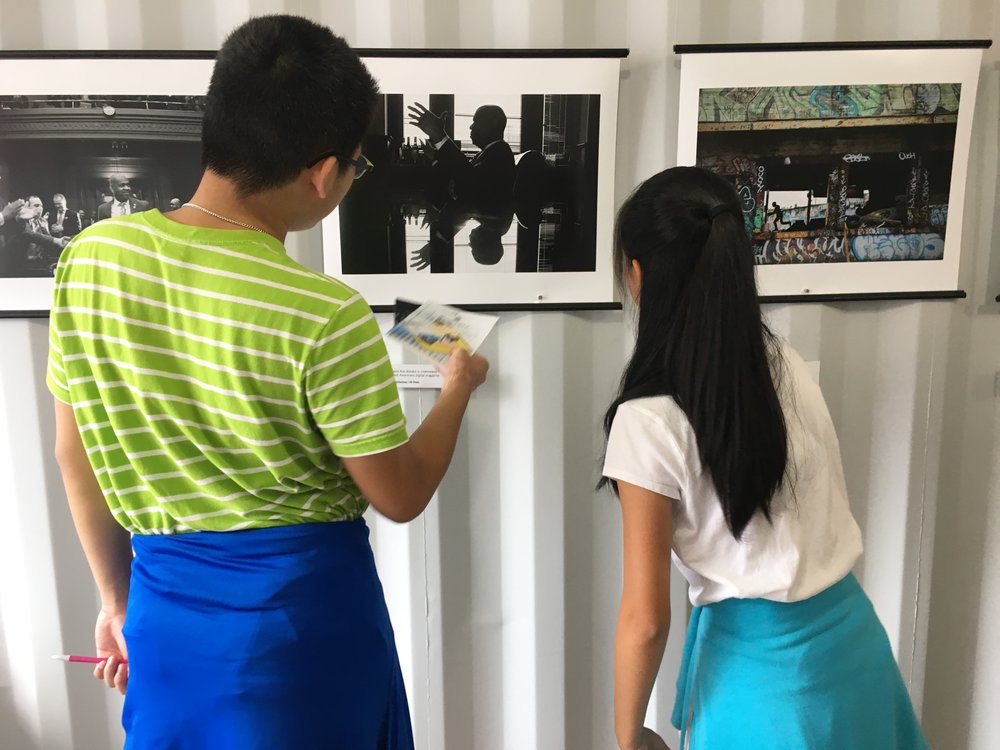 Students examine photos in the Newest Americans exhibit during Photoville's Education Day. Over 500 middle and high school students visited the photo village for an inside look at the exhibitions, artists and curators. (Photo by Julie Winokur)