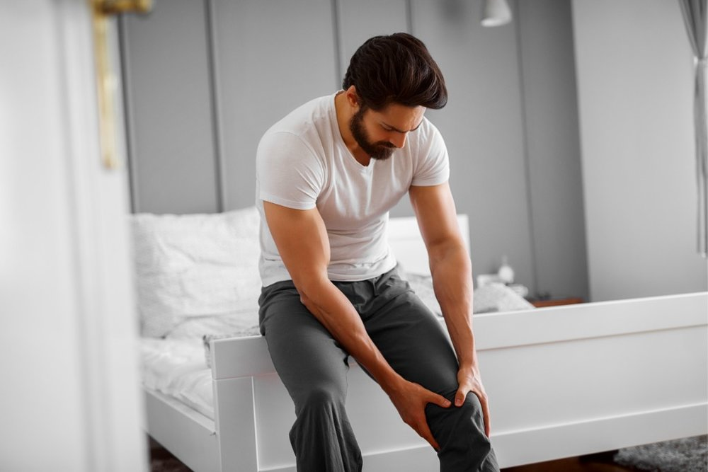 portrait-of-unhappy-handsome-muscular-bearded-man-having-knee-pain-picture-id912389656.jpg