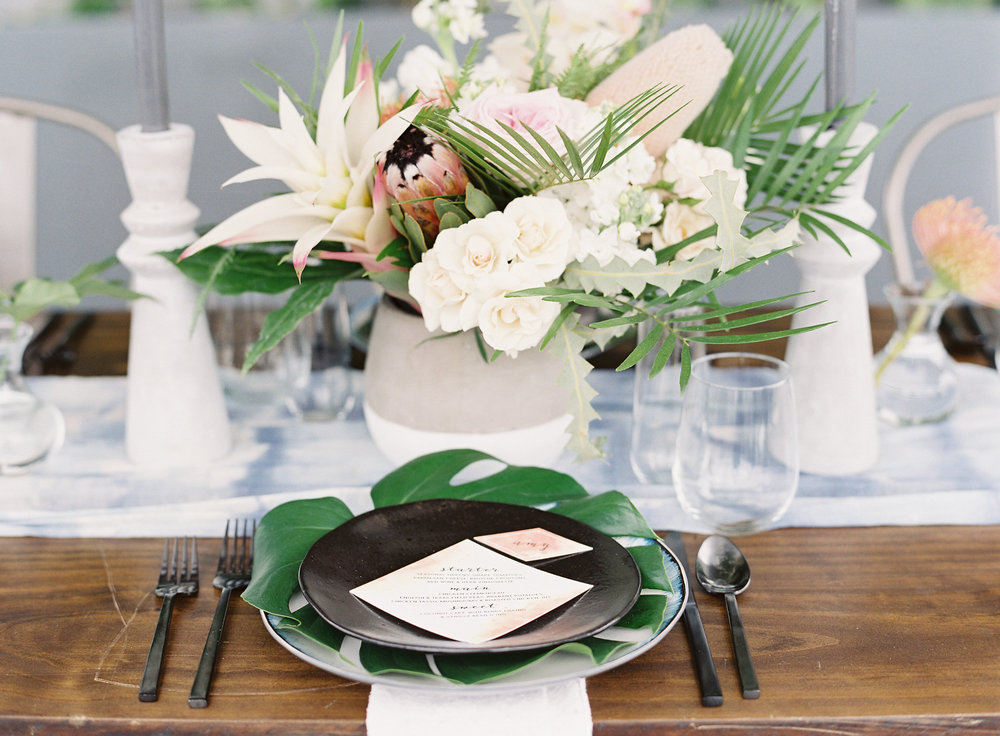 Soft blues mixed with black china, brushed metal flatware and opulent tropical floral makes for a wining combintation.