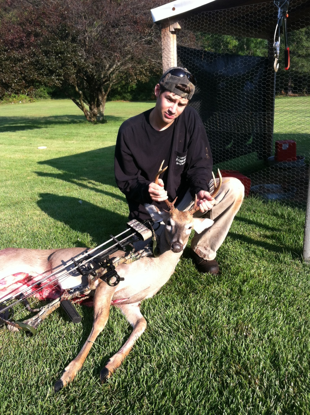 Example of bad photo  – This was my first bow kill, before I knew how to take a good photo. A chicken coop in the back ground? My butt isn't on the ground, I'm not wearing what I hunted in. Camera level too high. You can also see I have already gutted the animal and used my bow to try and cover it up, in turn, coving up the animal. My hands are in a poor position covering up the rack of my small, but first bow kill ever. A photo memory not really worth sharing. I didn't take the time.