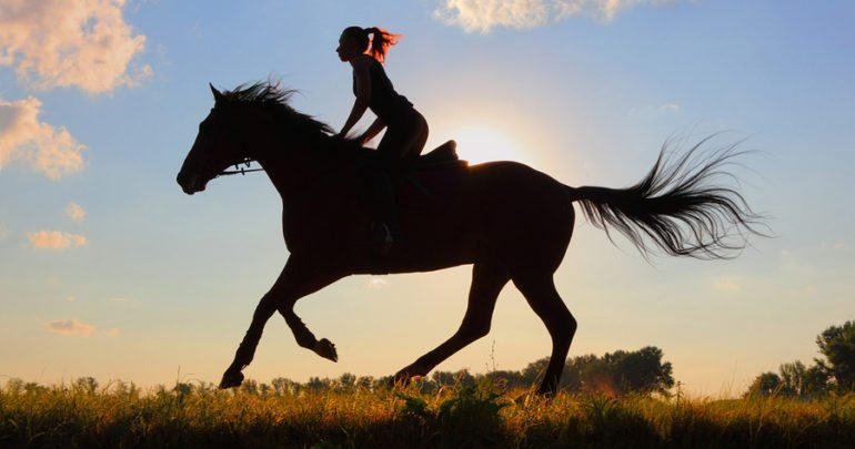 Girl horseback riding at sunset
