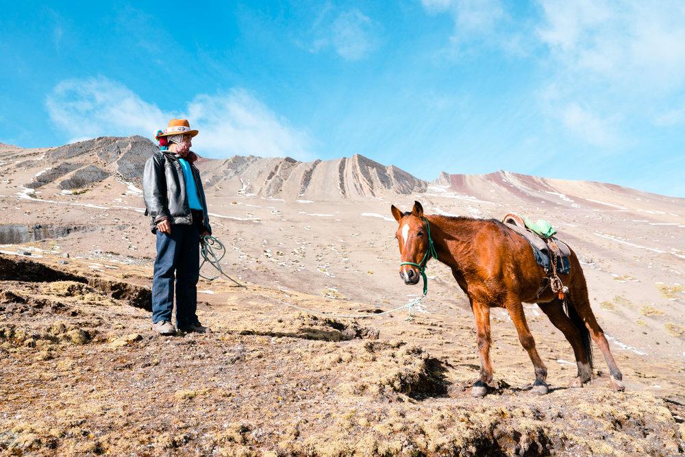 A man and his horse take a break on the mountain side. Rainbow Mountain, Cusco Area. Peru 2018