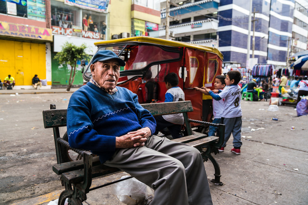 A elderly man sits away from the busy street markets. Gamarra, Lima. Peru 2018